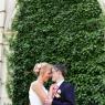 mariés face à facedevant un arche recouvert de lierre (Paris, 75)