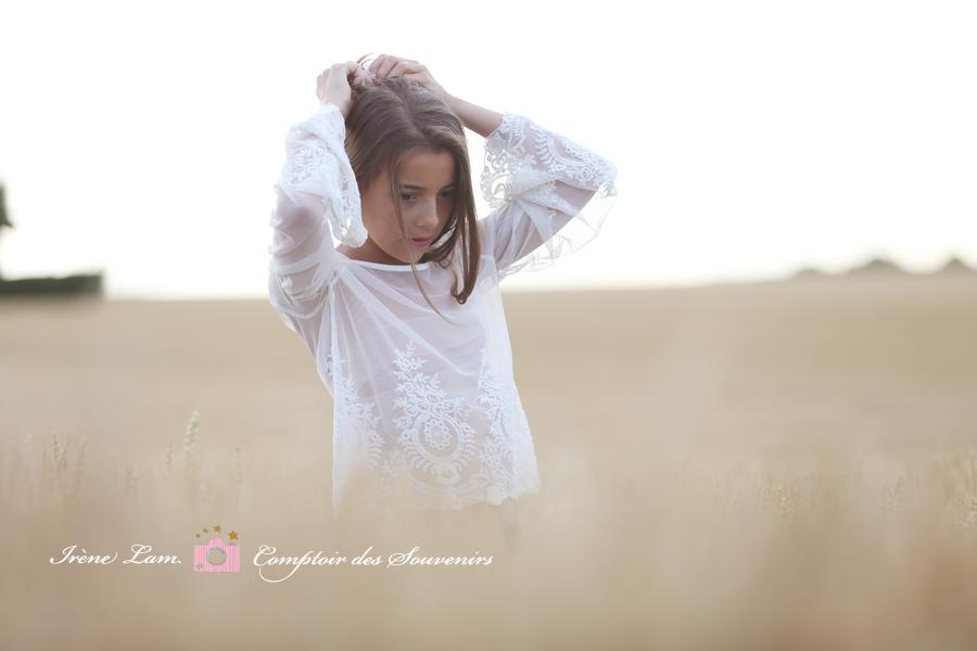 une fille se recoiffe dans les champs